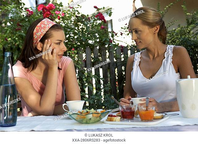 mother and daughter eating breakfast in the garden