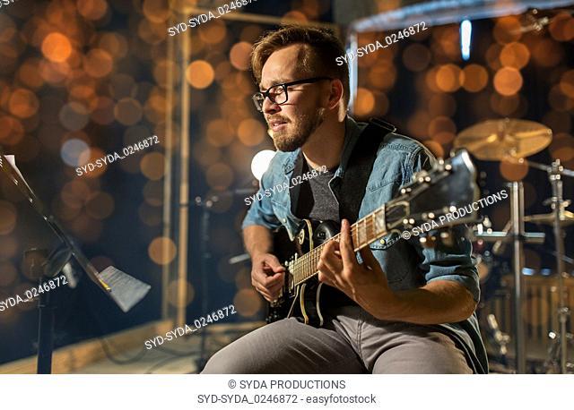 man playing guitar at studio or concert