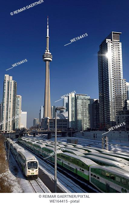 GO trains in downtown Toronto waiting for rush hour with CN tower, Rogers Centre stadium and highrise condominiums