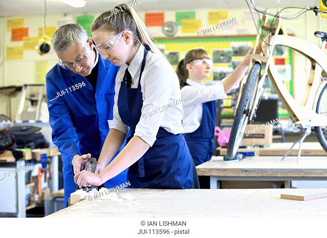 Teacher teaching high school student how to use wood plane tool in shop class