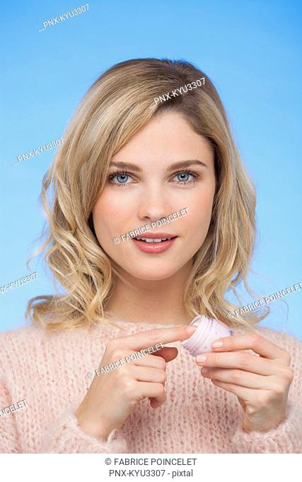 Portrait of a woman holding moisturizer cream