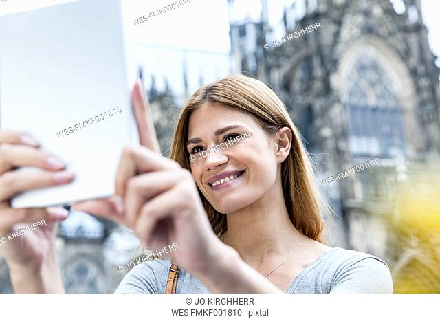 Germany, Cologne, portrait of smiling young woman taking a selfie in front of Cologne Cathedral