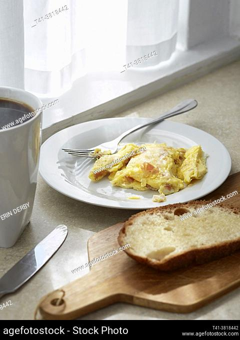 A kitchen counter with scrambled eggs, toast, coffee, and streaks of sunlight