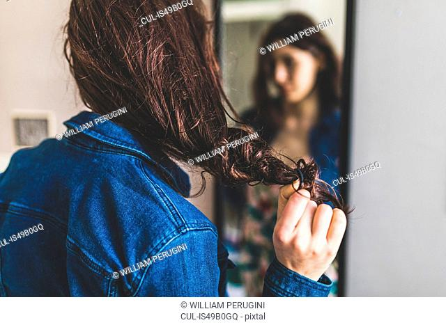 Young woman standing in front of mirror, pulling hair-band from hair, rear view