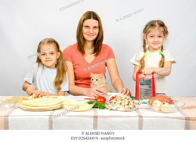 Mother and two little girls at a table prepared ingredients for the pizza. They were watching a cat