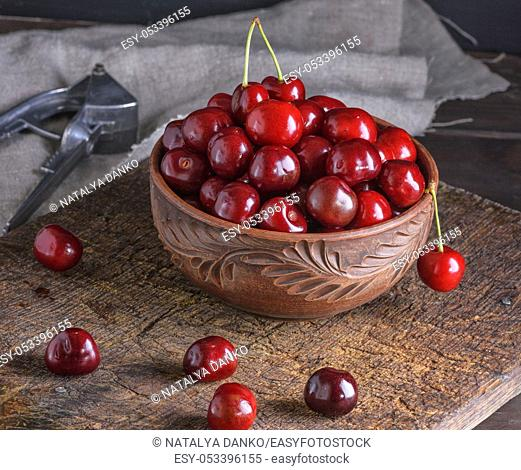 red ripe fresh cherry in a brown ceramic bowl on a wooden board, close up