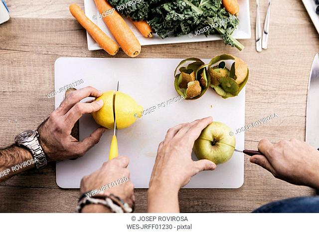 Hands of couple cutting fruits for preparing smoothies