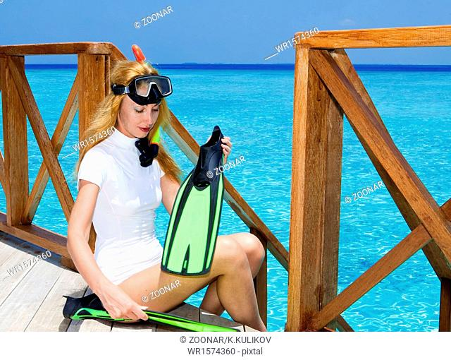 Young pretty woman with flippers, mask and tube