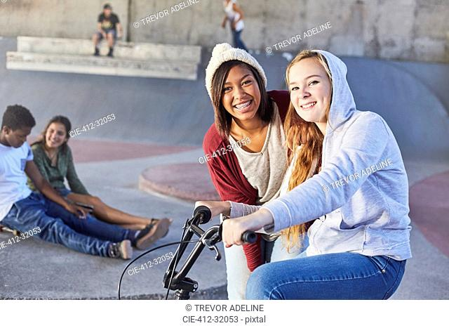 Portrait smiling teenage girls with BMX bicycle at skate park