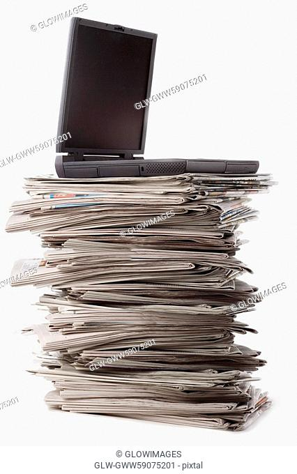 Close-up of a laptop on a stack of newspapers