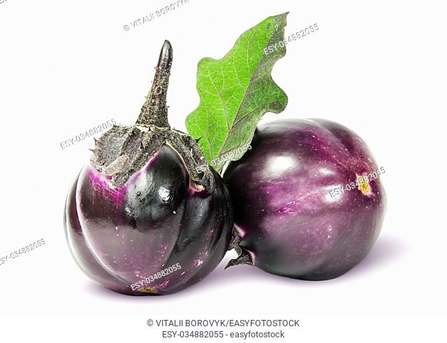 Two round ripe eggplant with green leaf isolated on white background