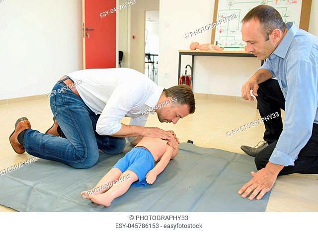 Man practicing resuscitation on a child dummy