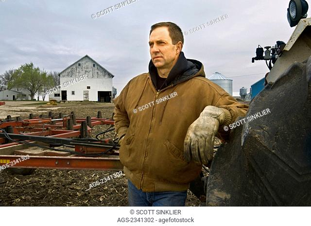 Agriculture - A farmer looks out across his field before beginning cultivating operations on a cold overcast Spring day, with farm buildings in the background /...