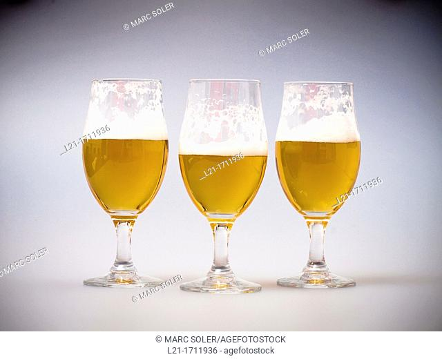 Three half-full glasses of beer