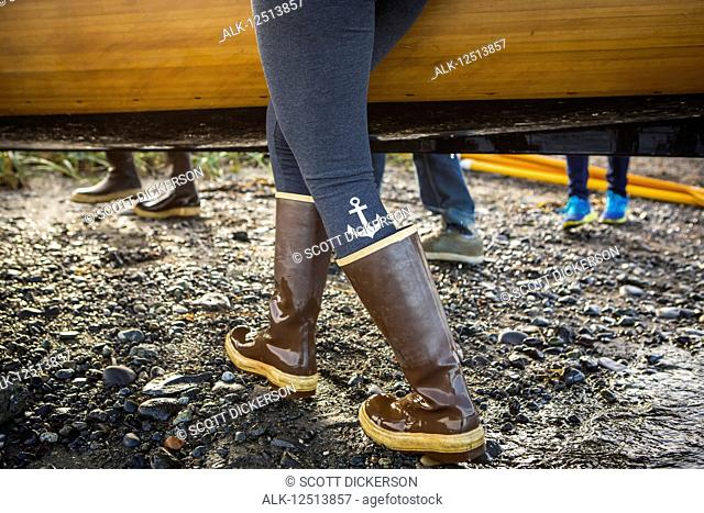 Close up of woman walking in rubber boots carrying a wooden boat, South-central Alaska; Homer, Alaska, United States of America