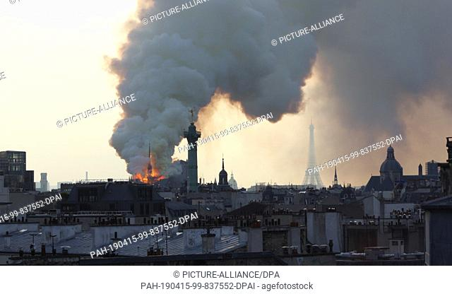 15 April 2019, France (France), Paris: A huge column of smoke stands above one of the world's most famous landmarks - Notre-Dame Cathedral in Paris