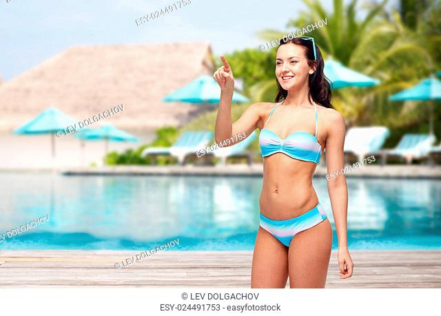 people, travel, tourism, swimwear and summer holidays concept - happy young woman in bikini swimsuit pointing to something imaginary over swimming pool and...