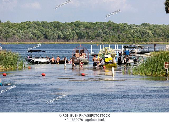 Young men and women boaters socialize on sandbar at Salt Springs Recreation Area in the Ocala National Forest, Florida