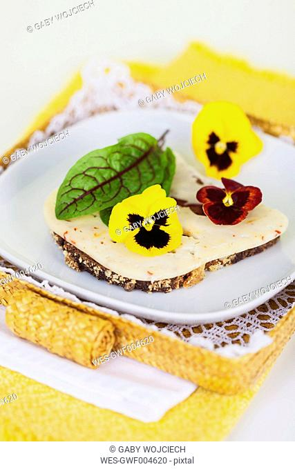 Slice of bread garnished with chili cheese, leaf of blood dock and pansies