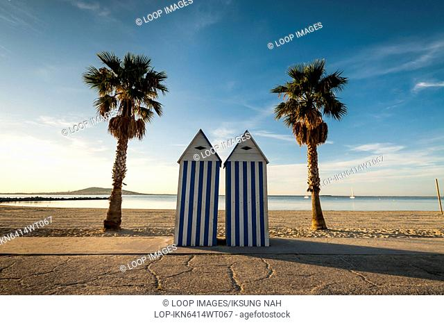 Beach huts and palm trees on the beach of Meze