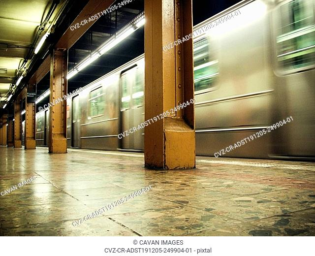 Interior view of subway moving through station in NYC