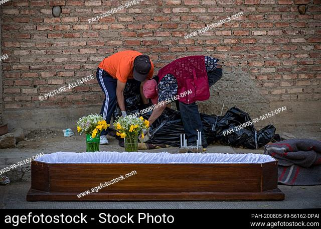 04 August 2020, Bolivia, Cochabamba: Residents are taking care of the body of Javier Ibanez, a 45-year-old man who died at home in the midst of the Corona...