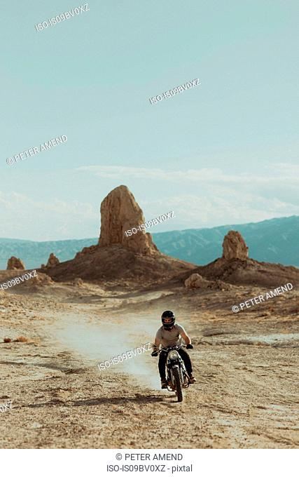 Motorcyclist riding in desert, Trona Pinnacles, California, US