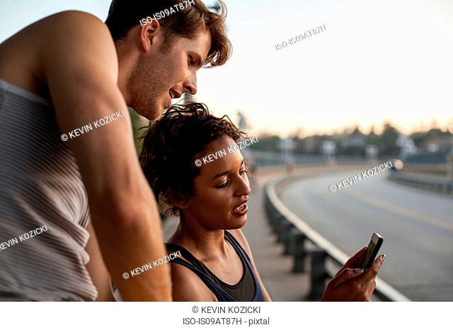 Joggers using cellular phone on bridge, Arroyo Seco Park, Pasadena, California, USA