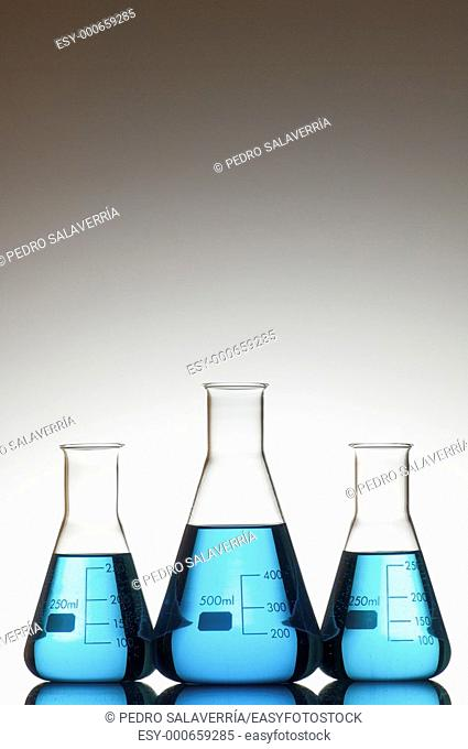 three flasks with liquid blue and white background