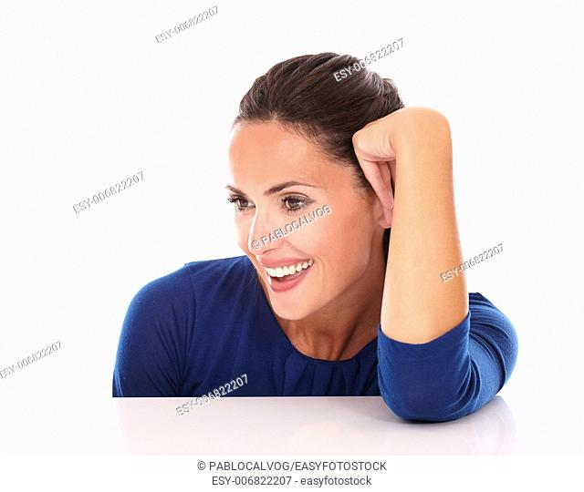 Charming hispanic looking to her right and smiling in white background - copyspace