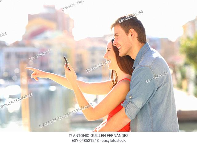 Couple checking phone pointing away on vacation