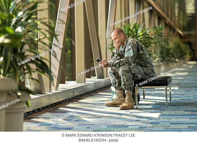 Caucasian soldier using cell phone in airport