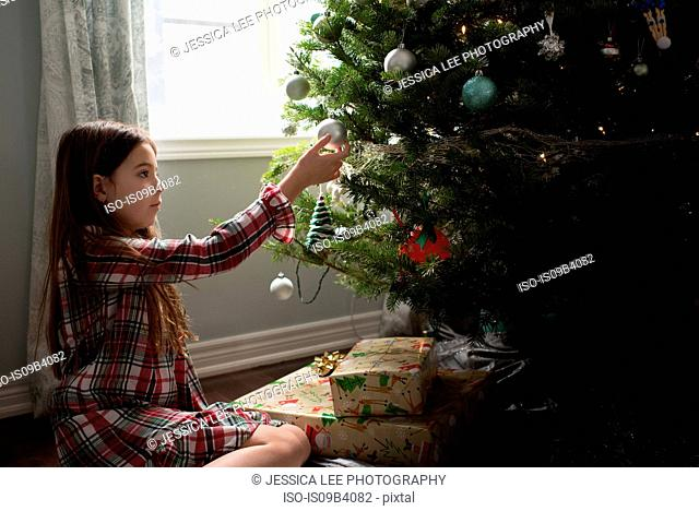 Girl decorating christmas tree with christmas decorations