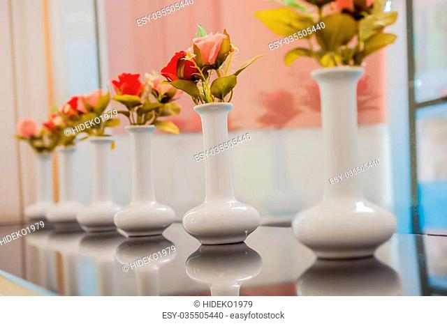 White vases with plastic colorful rose flowers