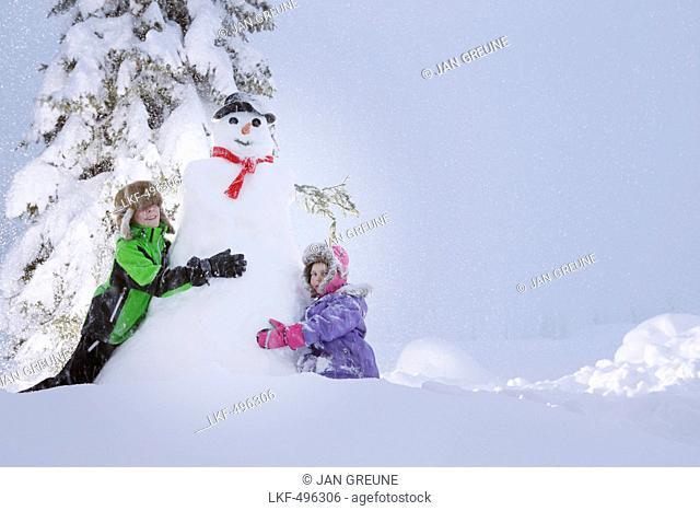 Children building a snowman, Passo Monte Croce di Comelico, South Tyrol, Italy