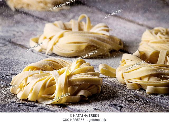 Variety of italian homemade raw uncooked pasta spaghetti and tagliatelle with sprinkling semolina flour over dark plank texture wooden table