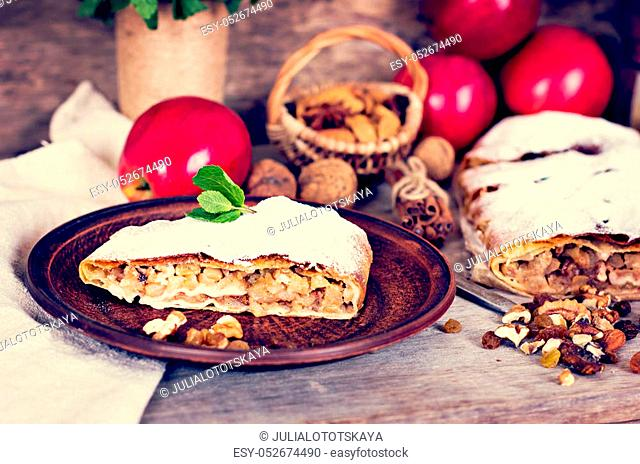 Sliced homemade apple strudel served with fresh apples, cinnamon sticks and sugar powder over old wooden background. Close up, dark rustic style Apple strudel
