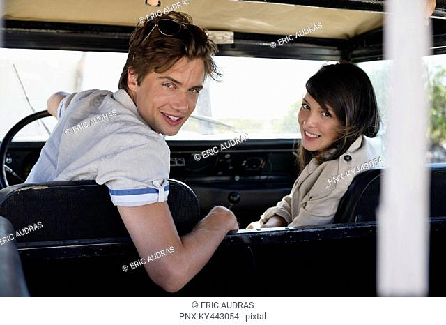Portrait of a couple sitting in a SUV and smiling