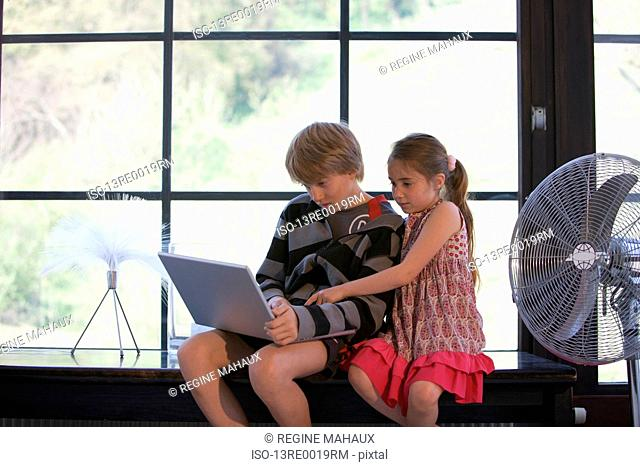 Girl and boy on computer at house