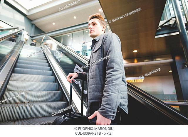 Young businessman commuter on escalator holding suitcase handle