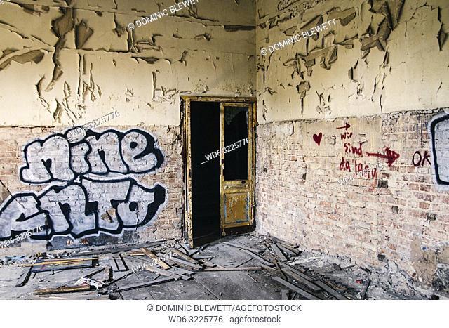Graffiti near a broken doorway in the abandoned Ballhaus Grunau, Berlin, Germany