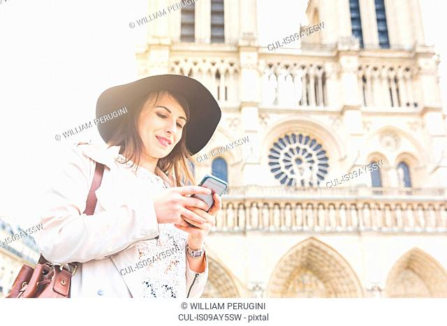 Stylish young woman reading smartphone at Notre Dame, Paris, France