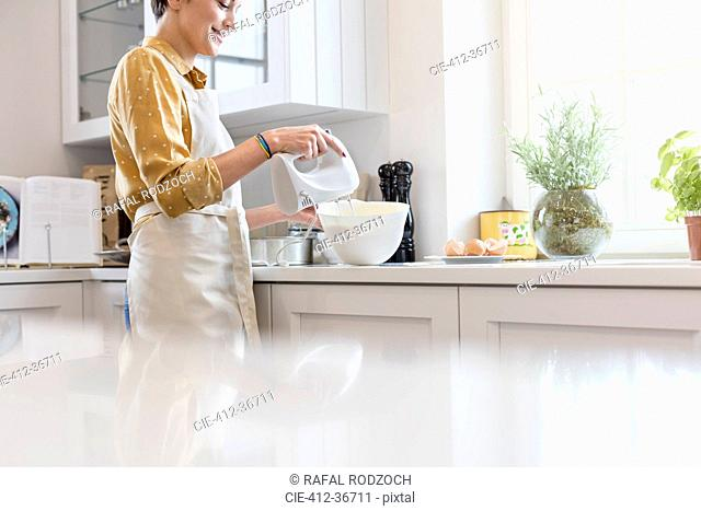 Woman baking, using electric hand mixer in kitchen