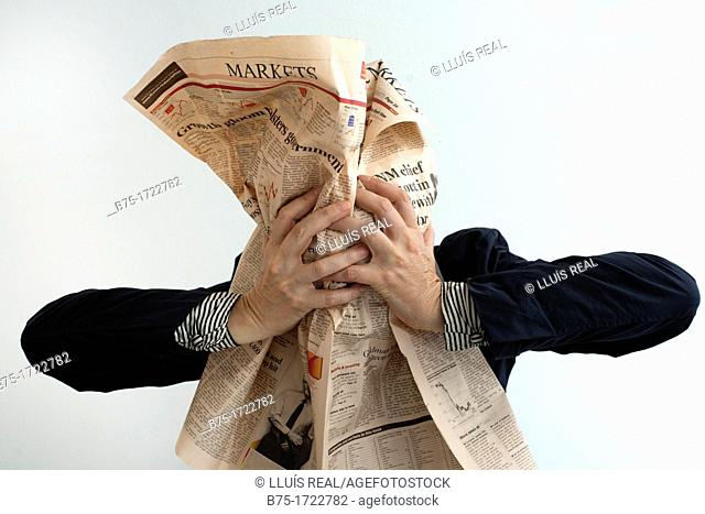 Mature woman covering her face with financial newspaper
