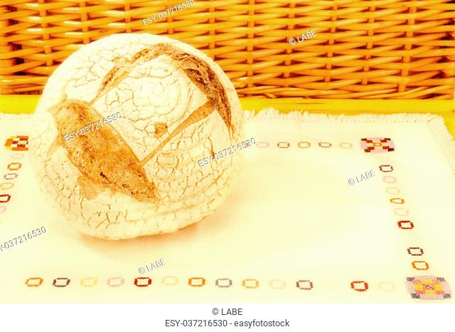 Ecological round bread made ??with a wooden table with embroidered tablecloth