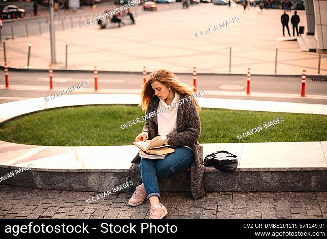 Teenage student girl reading book while sitting at campus in autumn