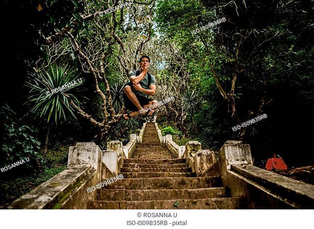 Man in mid air on steps to Mount Phousi, Luang Prabang, Laos