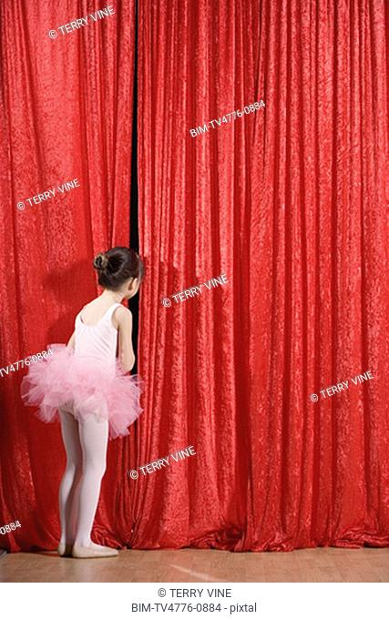 Asian girl in ballet outfit peeking through curtain