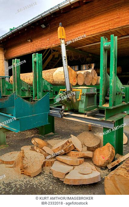 Large chain saw with cut segments of trunks, sawmill, timber trade, logs, timber storage, timber, high-quality construction timber, lumber, Vorarlberg, Austria
