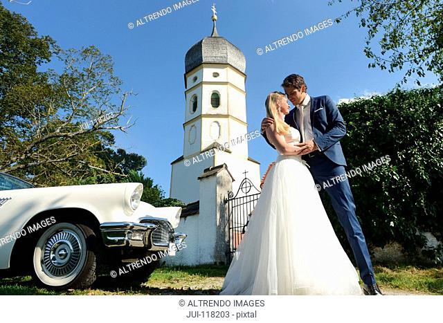 Bride And Groom Outside Church With Car On Wedding Day